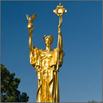Photo of a gilded sculpture in a park.